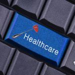 """Blue """"Healthcare"""" button on a keyboard close-up"""